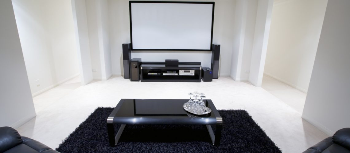 home theater room with black leather recliner chairs, black rug and table with wine glasses in front of large projection screen